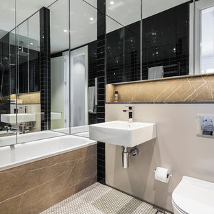 This is an example of a mid-sized contemporary master bathroom in Sydney with a drop-in tub, an open shower, a wall-mount toilet, black tile, ceramic tile, a wall-mount sink, white floor, an open shower, beige walls and mosaic tile floors.
