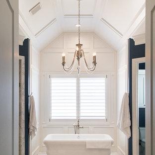 Klassisk inredning av ett mycket stort en-suite badrum, med luckor med profilerade fronter, vita skåp, ett fristående badkar, våtrum, en toalettstol med separat cisternkåpa, vita väggar, marmorgolv, grått golv och dusch med gångjärnsdörr