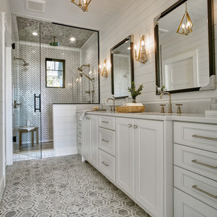Example of a mid-sized beach style master multicolored tile and marble tile gray floor, double-sink, shiplap ceiling, shiplap wall and marble floor alcove shower design in Other with recessed-panel cabinets, white cabinets, white walls, an undermount sink, a hinged shower door, white countertops, a built-in vanity, a one-piece toilet, quartzite countertops and a niche