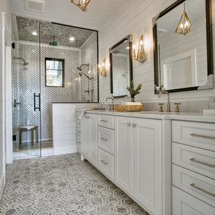他の地域の中くらいのビーチスタイルのおしゃれなマスターバスルーム (落し込みパネル扉のキャビネット、白いキャビネット、アルコーブ型シャワー、白い壁、アンダーカウンター洗面器、グレーの床、開き戸のシャワー、白い洗面カウンター、洗面台2つ、造り付け洗面台、塗装板張りの天井、塗装板張りの壁、一体型トイレ、マルチカラーのタイル、大理石タイル、大理石の床、珪岩の洗面台、ニッチ) の写真