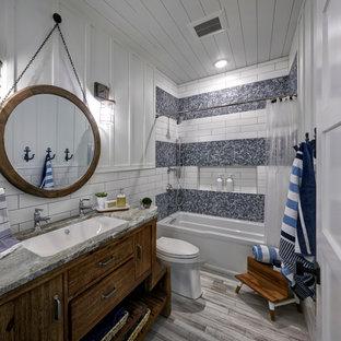 Inspiration för ett mellanstort maritimt grå grått badrum för barn, med släta luckor, skåp i mörkt trä, ett badkar i en alkov, en dusch/badkar-kombination, flerfärgad kakel, vita väggar, ett undermonterad handfat, beiget golv, dusch med duschdraperi, en toalettstol med separat cisternkåpa, glasskiva, cementgolv och granitbänkskiva
