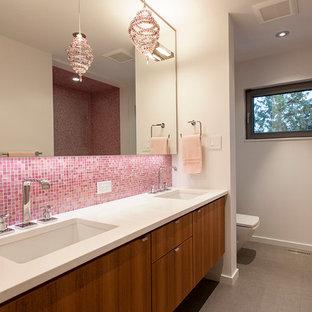 Foto de cuarto de baño contemporáneo con lavabo bajoencimera, armarios con paneles lisos, puertas de armario de madera oscura, baldosas y/o azulejos rosa y baldosas y/o azulejos en mosaico
