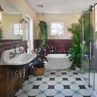 Cette photo montre une grand douche en alcôve principale éclectique avec une baignoire indépendante, un sol en carreaux de ciment, un lavabo suspendu, une cabine de douche à porte coulissante et boiseries.