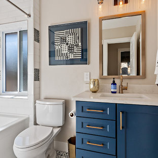 Example of a transitional 3/4 black and white tile multicolored floor bathroom design in Denver with recessed-panel cabinets, blue cabinets, a two-piece toilet, beige walls, an undermount sink and white countertops