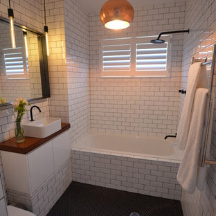 Ispirazione per una stanza da bagno design con lavabo a bacinella, vasca ad alcova, vasca/doccia, WC monopezzo, ante lisce, ante bianche, top in legno, piastrelle bianche, piastrelle diamantate, pavimento nero e top marrone