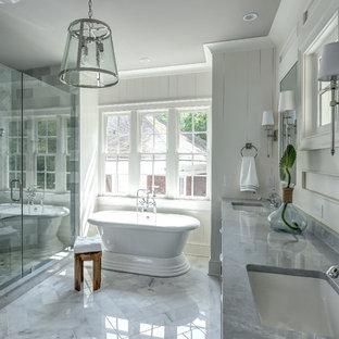 Imagen de cuarto de baño tradicional renovado con bañera exenta, ducha empotrada, baldosas y/o azulejos grises, paredes blancas, lavabo bajoencimera, suelo blanco, ducha con puerta con bisagras y encimeras grises
