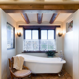 Southwest brown floor claw-foot bathtub photo in Albuquerque with beige walls