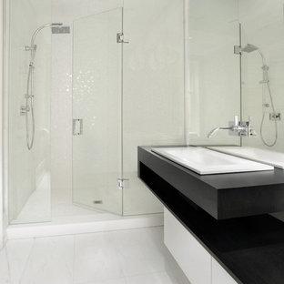 Foto di una stanza da bagno con doccia contemporanea di medie dimensioni con lavabo da incasso, ante lisce, ante bianche, doccia alcova, piastrelle bianche, pavimento in marmo, top in superficie solida, pavimento bianco e top nero