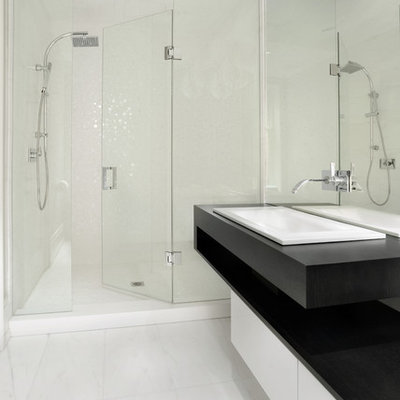 Example of a mid-sized trendy 3/4 white tile marble floor and white floor alcove shower design in Toronto with a drop-in sink, flat-panel cabinets, white cabinets, solid surface countertops and black countertops