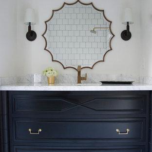 Inredning av ett klassiskt litet badrum, med ett undermonterad handfat, möbel-liknande, svarta skåp, marmorbänkskiva, ett badkar i en alkov, en dusch/badkar-kombination, en toalettstol med hel cisternkåpa, vit kakel, keramikplattor, vita väggar och klinkergolv i keramik
