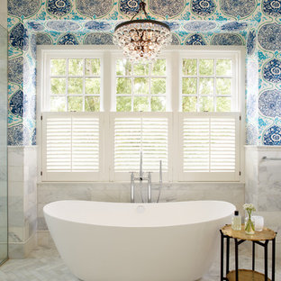 Example of an eclectic gray tile marble floor and gray floor freestanding bathtub design in Seattle with white cabinets, blue walls and a hinged shower door