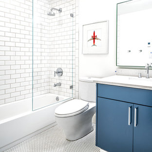 Bathroom - contemporary kids' white tile and subway tile mosaic tile floor, white floor and single-sink bathroom idea in Seattle with flat-panel cabinets, blue cabinets, a two-piece toilet, white walls, an undermount sink, a hinged shower door, white countertops and a floating vanity