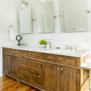Immagine di una stanza da bagno padronale tradizionale di medie dimensioni con lavabo sottopiano, ante in legno scuro, top in marmo, vasca con piedi a zampa di leone, doccia alcova, pareti grigie e parquet chiaro