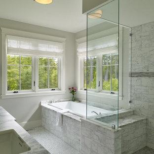 Ejemplo de cuarto de baño principal, tradicional renovado, grande, sin sin inodoro, con puertas de armario blancas, bañera esquinera, paredes grises, suelo de mármol, lavabo bajoencimera, suelo gris, ducha con puerta con bisagras y encimeras grises