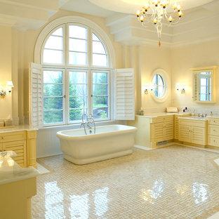 Immagine di una grande stanza da bagno padronale tradizionale con ante a persiana, ante gialle, vasca freestanding, doccia ad angolo, piastrelle bianche, piastrelle di marmo, pareti beige, pavimento in marmo, lavabo sottopiano, top in onice, pavimento multicolore e porta doccia a battente