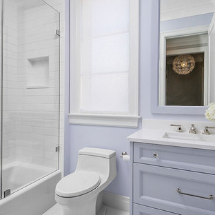 This is an example of a small traditional family bathroom in Chicago with recessed-panel cabinets, purple cabinets, an alcove bath, a shower/bath combination, a one-piece toilet, white tiles, marble tiles, purple walls, porcelain flooring, a submerged sink and engineered stone worktops.