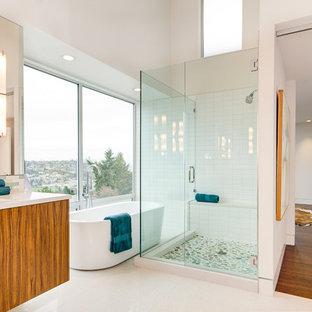 Ejemplo de cuarto de baño moderno con armarios con paneles lisos, puertas de armario de madera oscura, bañera exenta, suelo de baldosas tipo guijarro y suelo blanco