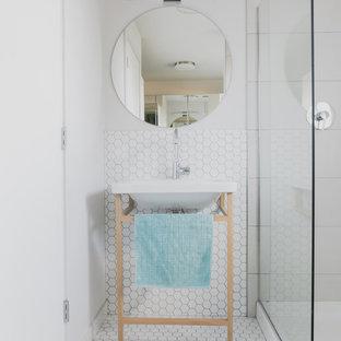 Modelo de cuarto de baño principal, vintage, pequeño, con armarios abiertos, puertas de armario de madera clara, ducha abierta, sanitario de dos piezas, baldosas y/o azulejos blancos, baldosas y/o azulejos en mosaico, paredes blancas, suelo con mosaicos de baldosas y lavabo tipo consola