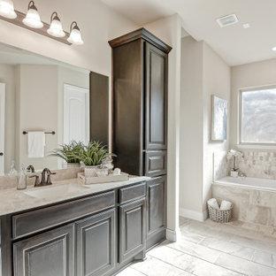 ヒューストンのトランジショナルスタイルのおしゃれなマスターバスルーム (レイズドパネル扉のキャビネット、濃色木目調キャビネット、ドロップイン型浴槽、マルチカラーのタイル、ベージュの壁、アンダーカウンター洗面器、マルチカラーの床、ベージュのカウンター) の写真