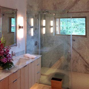 Diseño de cuarto de baño principal, de estilo zen, grande, con armarios con paneles lisos, puertas de armario de madera clara, ducha doble, baldosas y/o azulejos grises, baldosas y/o azulejos de mármol, paredes beige, suelo de bambú, lavabo encastrado, encimera de granito, suelo beige, ducha con puerta corredera y encimeras beige