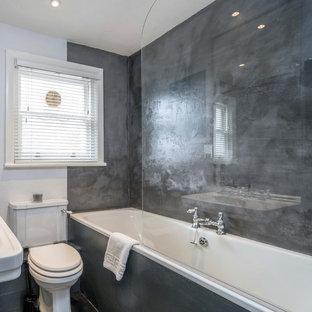 Foto di una stanza da bagno per bambini chic di medie dimensioni con vasca da incasso, vasca/doccia, WC monopezzo, piastrelle grigie, piastrelle di cemento, pareti grigie, pavimento in legno verniciato e top in cemento