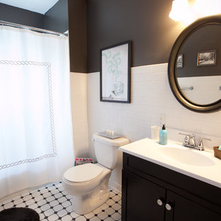 Elegant subway tile and black and white tile bathroom photo in Omaha with black walls