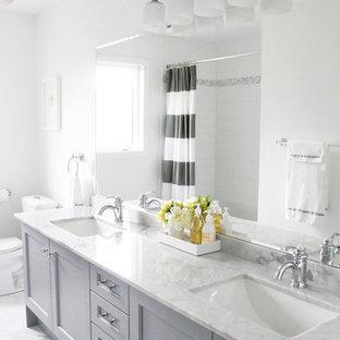 Imagen de cuarto de baño clásico con encimera de mármol, lavabo bajoencimera y puertas de armario grises