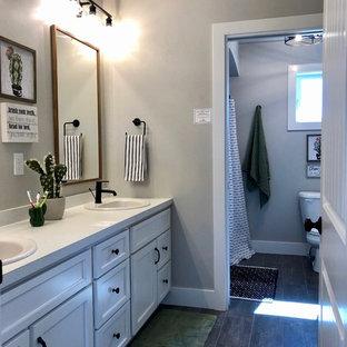 Modelo de cuarto de baño infantil, de estilo de casa de campo, de tamaño medio, con armarios estilo shaker, puertas de armario blancas, combinación de ducha y bañera, sanitario de una pieza, paredes grises, suelo vinílico, lavabo encastrado, encimera de laminado, suelo negro, ducha con cortina y encimeras blancas