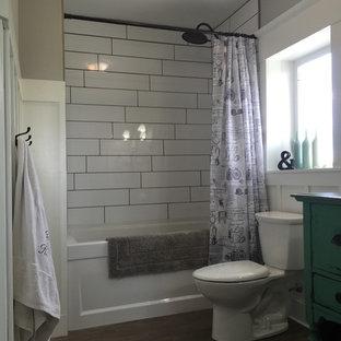 Lantlig inredning av ett mellanstort turkos turkost badrum, med möbel-liknande, turkosa skåp, ett badkar i en alkov, en dusch/badkar-kombination, en toalettstol med separat cisternkåpa, vit kakel, keramikplattor, grå väggar, klinkergolv i keramik, ett nedsänkt handfat, träbänkskiva, grått golv och dusch med duschdraperi