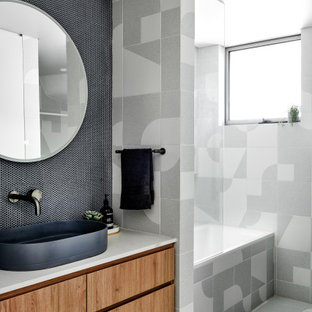 Inspiration for a mid-sized scandinavian bathroom in Sydney with medium wood cabinets, a drop-in tub, a shower/bathtub combo, blue tile, porcelain tile, porcelain floors, a vessel sink, engineered quartz benchtops and grey floor.