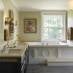 Inspiration for a mediterranean gray tile and stone tile drop-in bathtub remodel in Philadelphia with an undermount sink, furniture-like cabinets, dark wood cabinets and limestone countertops