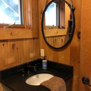 ポートランド(メイン)の小さいおしゃれな浴室 (シェーカースタイル扉のキャビネット、青いキャビネット、段差なし、一体型トイレ、マルチカラーの壁、セラミックタイルの床、オーバーカウンターシンク、御影石の洗面台、マルチカラーの床、引戸のシャワー、黒い洗面カウンター) の写真