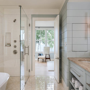 Design ideas for a large beach style master bathroom in Portland Maine with flat-panel cabinets, blue cabinets, a curbless shower, white tile, subway tile, blue walls, an undermount sink, a freestanding tub, marble floors, granite benchtops and a hinged shower door.