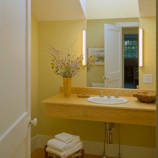 Esempio di una stanza da bagno classica di medie dimensioni con lavabo da incasso, top in legno, pareti gialle e pavimento in linoleum