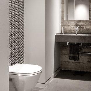 Foto di una stanza da bagno con doccia industriale di medie dimensioni con piastrelle grigie, piastrelle nere, pavimento in cemento, lavabo sottopiano, WC sospeso, piastrelle a mosaico, pareti grigie e top in cemento