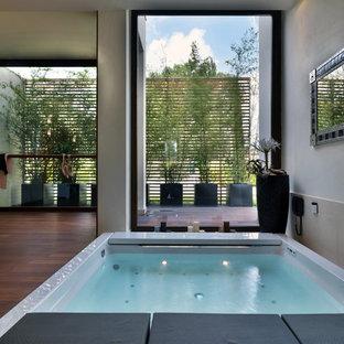 Modernes Badezimmer mit Whirlpool und braunem Holzboden in Bologna