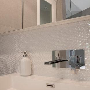 モントリオールの中サイズのモダンスタイルのおしゃれなマスターバスルーム (フラットパネル扉のキャビネット、白いキャビネット、珪岩の洗面台、アルコーブ型シャワー、グレーのタイル、セラミックタイル、セラミックタイルの床) の写真