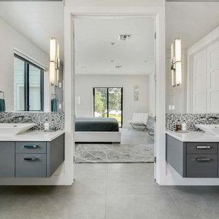 Esempio di una grande stanza da bagno padronale design con ante lisce, ante grigie, doccia alcova, WC monopezzo, piastrelle grigie, piastrelle di vetro, pareti bianche, pavimento in gres porcellanato, lavabo a bacinella, top in quarzo composito e pavimento grigio