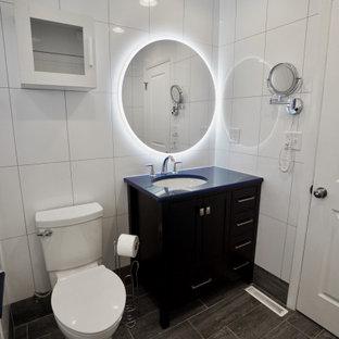 Idee per una piccola stanza da bagno padronale minimal con ante in stile shaker, ante nere, vasca ad alcova, vasca/doccia, WC monopezzo, piastrelle bianche, piastrelle in ceramica, pareti bianche, pavimento con piastrelle in ceramica, lavabo sottopiano, top in quarzite, pavimento grigio, porta doccia scorrevole, top blu, panca da doccia, un lavabo e mobile bagno freestanding