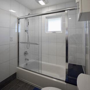 Idéer för små funkis blått en-suite badrum, med skåp i shakerstil, svarta skåp, ett badkar i en alkov, en dusch/badkar-kombination, en toalettstol med hel cisternkåpa, vit kakel, keramikplattor, vita väggar, klinkergolv i keramik, ett undermonterad handfat, bänkskiva i kvartsit, grått golv och dusch med skjutdörr