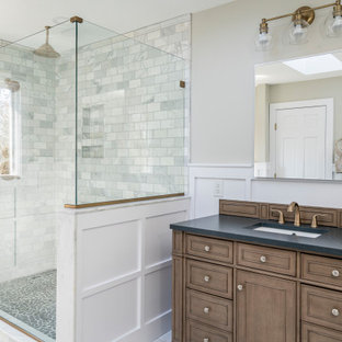 Alcove shower - transitional 3/4 multicolored tile and subway tile multicolored floor, single-sink and wainscoting alcove shower idea in Other with recessed-panel cabinets, medium tone wood cabinets, beige walls, an undermount sink, a hinged shower door, black countertops and a built-in vanity