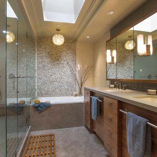 Ispirazione per una stanza da bagno design con lavabo sottopiano, vasca ad alcova, doccia alcova, ante lisce, ante in legno scuro, piastrelle grigie e piastrelle di ciottoli