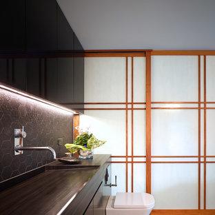 Foto de cuarto de baño principal, de estilo zen, grande, con armarios con paneles lisos, puertas de armario negras, sanitario de una pieza y lavabo de seno grande