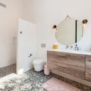 Exemple d'une grand salle d'eau tendance avec une douche ouverte, un mur blanc, un sol en galet, un lavabo intégré, aucune cabine, un placard à porte plane, des portes de placard en bois brun, un bidet et un plan de toilette en surface solide.