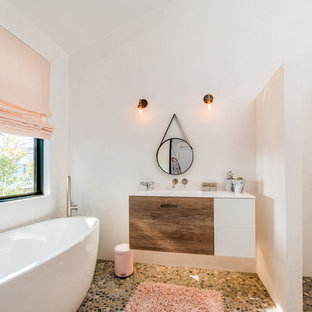 Inspiration for a large contemporary 3/4 pebble tile floor bathroom remodel in Los Angeles with white walls, an integrated sink, flat-panel cabinets, medium tone wood cabinets and solid surface countertops