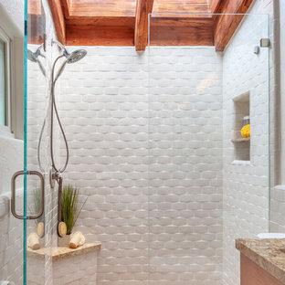 Immagine di una stanza da bagno con doccia mediterranea di medie dimensioni con piastrelle bianche, piastrelle in ceramica, pareti bianche, doccia alcova e porta doccia a battente