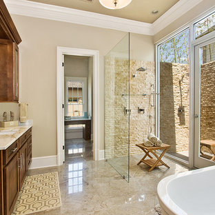 Inspiration for a transitional beige tile and stone tile beige floor bathroom remodel in New Orleans with an undermount sink, shaker cabinets and dark wood cabinets