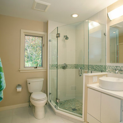 Corner shower - mid-sized traditional master green tile and ceramic tile ceramic tile and white floor corner shower idea in Philadelphia with a vessel sink, flat-panel cabinets, white cabinets, beige walls and a two-piece toilet