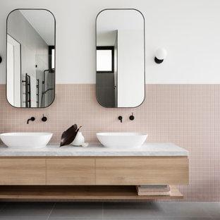 メルボルンのコンテンポラリースタイルのおしゃれな浴室 (フラットパネル扉のキャビネット、淡色木目調キャビネット、置き型浴槽、ピンクのタイル、モザイクタイル、白い壁、ベッセル式洗面器、グレーの床、白い洗面カウンター、洗面台2つ、フローティング洗面台) の写真