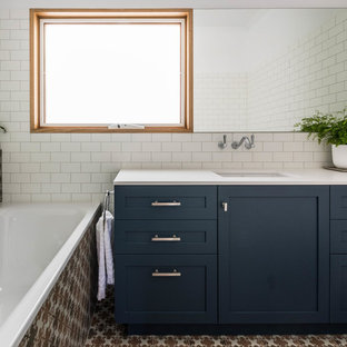 Inspiration for a transitional 3/4 bathroom in Melbourne with shaker cabinets, blue cabinets, a drop-in tub, white tile, ceramic tile, white walls, cement tiles, an undermount sink, multi-coloured floor and beige benchtops.